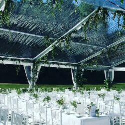 Tält med transparent tak och Chiavari-stolen med vit dyna. Perfekt att sitta på under en lång bröllopsmiddag.